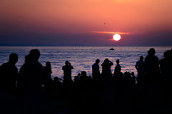 Schattenbilder von den Leuten, die Sonnenuntergang über dem Meer O aufpassen und filmen Stockfoto