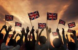 Schattenbilder von den Leuten, die Staatsflagge von Großbritannien halten Stockfotos