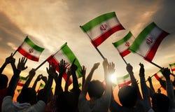 Schattenbilder von den Leuten, welche die Flagge vom Iran halten Lizenzfreies Stockbild