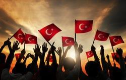 Schattenbilder von den Leuten, welche die Flagge von der Türkei halten Stockfoto
