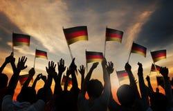 Schattenbilder von den Leuten, welche die Flagge von Deutschland halten Stockfoto