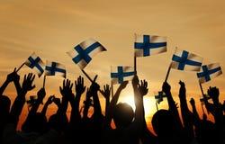 Schattenbilder von den Leuten, welche die Flagge von Finnland halten Lizenzfreies Stockfoto