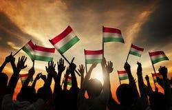 Schattenbilder von den Leuten, welche die Flagge von Ungarn halten Stockfoto