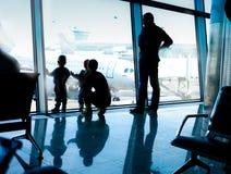 Schattenbilder von den Leuten, welche die Flugzeuge in einem internationa betrachten stockbild
