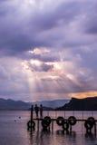 Schattenbilder von den Männern und von Frauen, die auf dem Pier im backgro stehen Lizenzfreie Stockfotografie