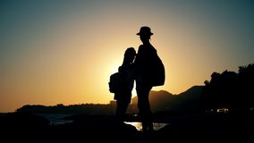 Schattenbilder von den Mutter- und Kindertouristen, die bei Sonnenuntergang wandern Mutter und Tochter auf tragenden Rucksäcken d stock footage