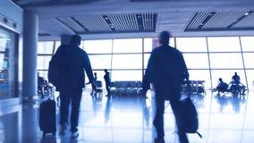 Schattenbilder von den Passagieren, die in einen Flughafen gehen Lizenzfreie Stockfotografie