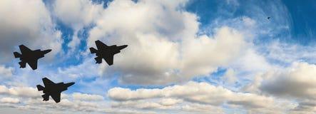 Schattenbilder von drei Flugzeugen F-35 gegen den blauen Himmel Stockfotografie