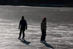 Schattenbilder von Eisschlittschuhläufern Lizenzfreie Stockfotos