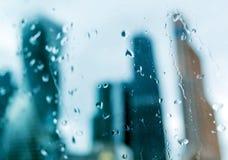 Schattenbilder von Gebäudetürmen hinter nassem Glas Stockfotografie