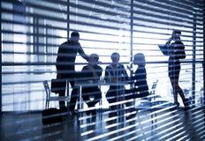 Schattenbilder von Geschäftsleuten durch die Vorhänge Lizenzfreie Stockfotos