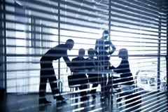 Schattenbilder von Geschäftsleuten durch die Vorhänge Lizenzfreie Stockbilder