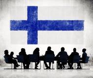 Schattenbilder von Geschäftsleuten und eine Flagge von Finnland Stockfotografie