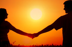 Schattenbilder von glücklichen lächelnden jungen Paaren auf dem Sommerweizengebiet stockfoto