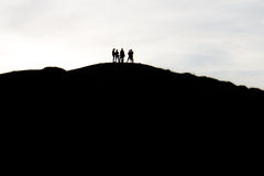 Schattenbilder von Leuten in der Spitze eines Berges Lizenzfreies Stockbild