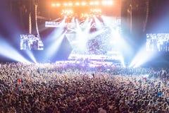 Schattenbilder von Leuten in einem hellen im Poprockkonzert vor dem Stadium Hände mit Geste Hörnern Das schaukelt Partei in a Lizenzfreie Stockfotografie