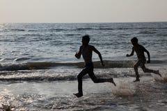 Schattenbilder von Leuten spielen in den Wellen im Bekal-Strand lizenzfreie stockbilder
