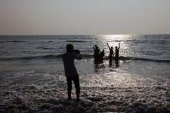 Schattenbilder von Leuten spielen in den Wellen im Bekal-Strand lizenzfreies stockfoto