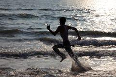 Schattenbilder von Leuten spielen in den Wellen im Bekal-Strand stockfotografie