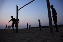 Schattenbilder von Leuten spielen Fußball im Strand stockfotos