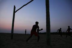 Schattenbilder von Leuten spielen Fußball im Strand lizenzfreies stockfoto