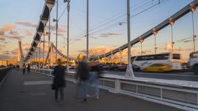 Schattenbilder von Leuten und von Autos auf der Stahlbrücke Stockfotografie
