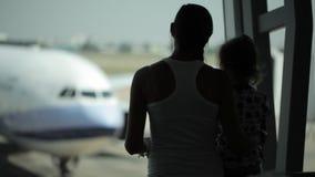Schattenbilder von Mutter ahd Tochter mit Flugzeug auf dem Hintergrund stock video
