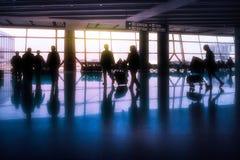 Schattenbilder von Passagieren in einem asiatischen Flughafen mit dem Sonne shini Lizenzfreies Stockbild