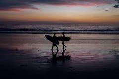 Schattenbilder von Surfern bei Sonnenuntergang lizenzfreies stockfoto