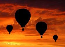 Schattenbilder von vier Heißluftballonen im Sonnenaufgang Stockfotografie