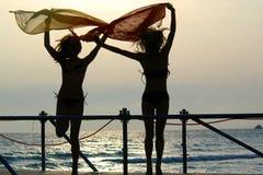 Schattenbilder von zwei Mädchen, die mit Schals tanzen Stockbild