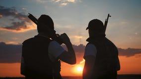 Schattenbilder von zwei Soldaten mit Waffe gegen einen Sonnenuntergang stock footage