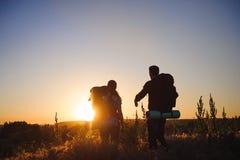 Schattenbilder von zwei Wanderern mit Rucksäcken gehend bei Sonnenuntergang Trekking und Genießen der Sonnenuntergangansicht stockbild