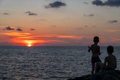 Schattenbilder zwei Jungen, die Sonne bei Sonnenuntergang auf dem Strand aufpassen stockfotografie