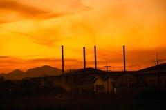 Schattenbildfabrikkamin mit Dämmerungshimmel Stockfotografie