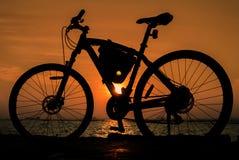 Schattenbildfahrrad mit Sonnenunterganghimmel Lizenzfreies Stockfoto