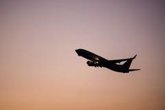Schattenbildfliegenflugzeug während Sonnenuntergang Stockbild