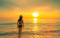 Schattenbildfrau, die in tropischem Meer mit schönem Sonnenunterganghimmel am Paradiesstrand geht Glücklicher Mädchenabnutzungsbi lizenzfreie stockfotos