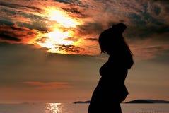 Schattenbildfrau und -sonnenuntergang auf dem Strand Lizenzfreie Stockbilder
