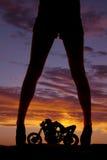 Schattenbildfrauen-Beinmotorrad darunter lizenzfreie stockfotografie