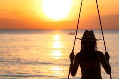 Schattenbildfrauenabnutzungsbikini- und -strohhutschwingen das Schwingen am Strand auf Sommerferien bei Sonnenuntergang Genießen  stockfotos