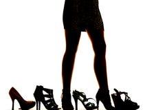 Schattenbildfrauenbeine mit vielen Schuhen Stockfotografie