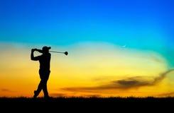 Schattenbildgolfspieler, der Golf bei schönem Sonnenuntergang spielt Stockfotografie
