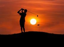 Schattenbildgolfspieler, der Golfball bei Sonnenuntergang schlägt Stockfotografie