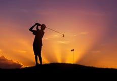 Schattenbildgolfspieler, der Golfball bei Sonnenuntergang schlägt Lizenzfreies Stockfoto