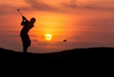 Schattenbildgolfspieler, der Golfball im Sonnenuntergang schlägt Lizenzfreies Stockbild