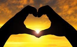 Schattenbildhände in Form von Herzen Stockfoto