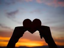 Schattenbildhand hebt das rote Papierherz mit Unschärfesonnenlicht während des Sonnenuntergangs an, Lizenzfreies Stockfoto