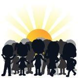 Schattenbildkinder und steigende Sonne Stockfoto