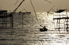 Schattenbildleute auf Boot bei Sonnenuntergang Stockbild